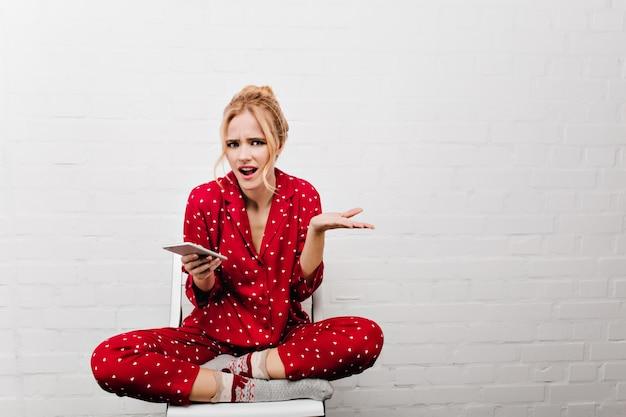 Niezadowolona blondynka trzyma smartfon. zły modelka w czerwonej piżamie siedzi ze skrzyżowanymi nogami na jasnej ścianie.