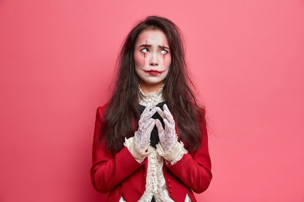 Niezadowolona brunetka kobieta wygląda nieszczęśliwie powyżej ma przerażający makijaż ubrany w kostium karnawałowy, steepluje palce z jaskraworóżową ścianą, przygotowuje się do imprezy z okazji halloween