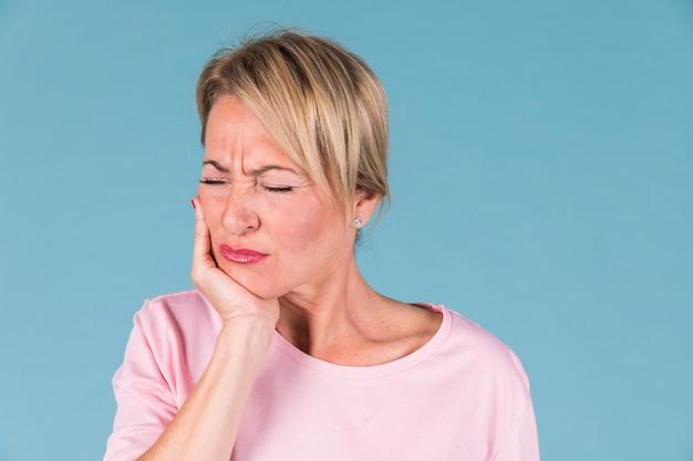 Niezadowolona chora kobieta mająca ból zęba i dotykająca jego policzka