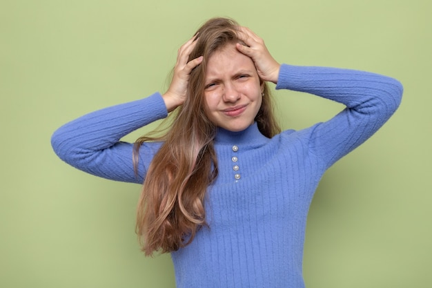 Niezadowolona chwyciła głowę piękna mała dziewczynka ubrana w niebieski sweter na oliwkowozielonej ścianie