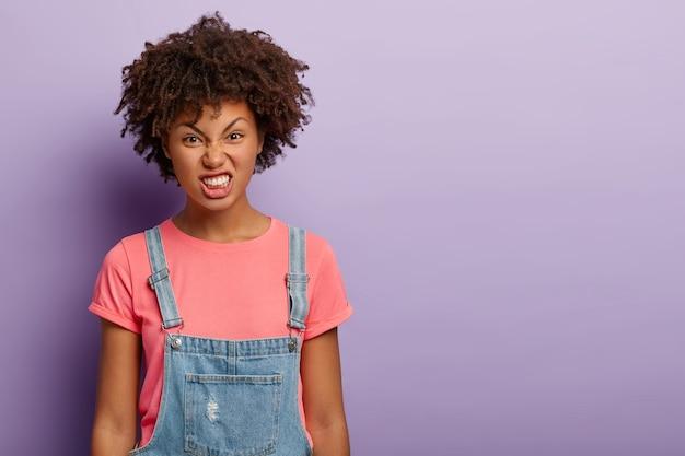 Niezadowolona ciemnoskóra kobieta z kręconą fryzurą, uśmiechnięta twarz, zaciska zęby, traci panowanie nad sobą, ubrana w swobodny strój