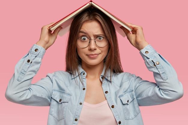 Niezadowolona ciemnowłosa kobieta wygląda z niezadowoloną miną, czuje się zmęczona ciągłą nauką, trzyma książkę nad głową, nosi dżinsową koszulę, okulary optyczne, domaga się wakacji, odizolowana na różowej ścianie