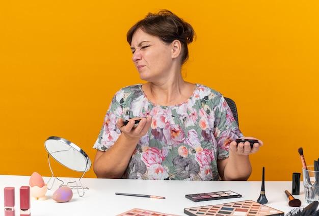 Niezadowolona dorosła kobieta rasy kaukaskiej siedząca przy stole z narzędziami do makijażu trzymająca rumieniec odizolowana na pomarańczowej ścianie z miejscem na kopię