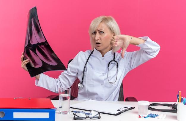 Niezadowolona dorosła lekarka w szacie medycznej ze stetoskopem siedząca przy biurku z narzędziami biurowymi trzymająca wynik prześwietlenia i kciukiem w dół odizolowana na różowej ścianie z kopią miejsca