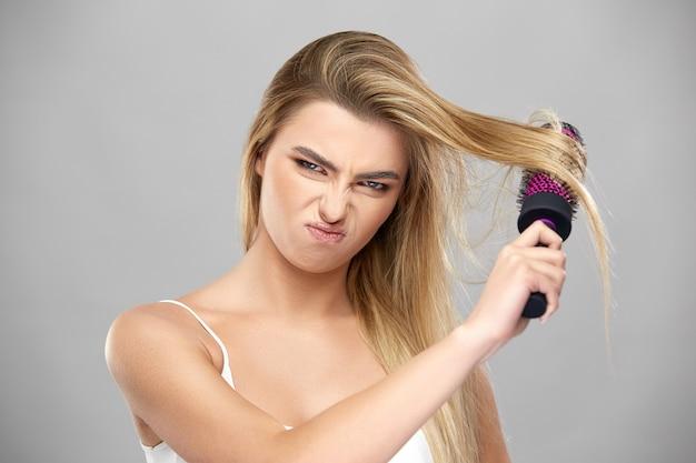 Niezadowolona dziewczyna czesząca swoje długie jasnobrązowe włosy, śliczna dziewczyna zła na czesanie włosów