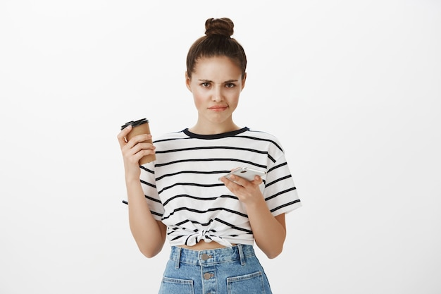 Niezadowolona dziewczyna robiąca zakupy online w aplikacji na telefon komórkowy, przewijająca profile aplikacji randkowej i uśmiechająca się rozczarowana pijąc kawę