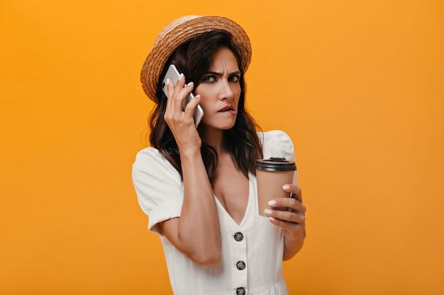 Niezadowolona dziewczyna rozmawia przez telefon na pomarańczowym tle i trzyma szklankę kawy