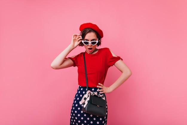 Niezadowolona dziewczyna w czarnej torebce pozuje we francuskim berecie. portret szczupła kobieta w czerwonym stroju na białym tle.