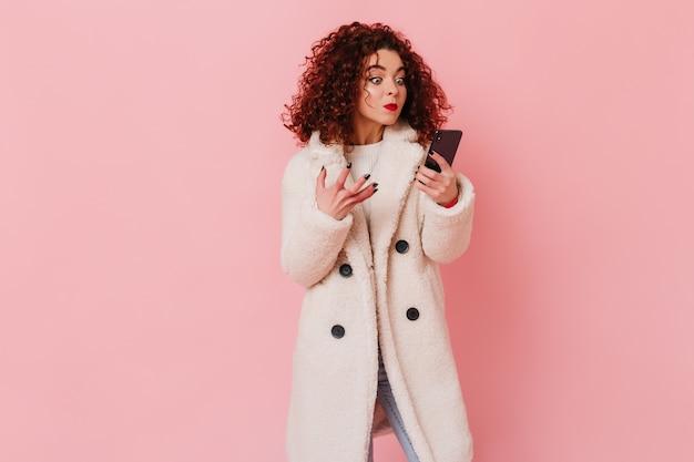 Niezadowolona dziewczyna wygląda na zły na ekranie telefonu. portret kobiety z kręconymi ustami, ubrana w biały płaszcz na różowej przestrzeni.