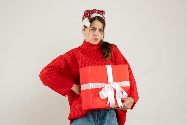 Niezadowolona dziewczyna z santa hat trzyma obecny kładąc rękę na talii stojącej na białym