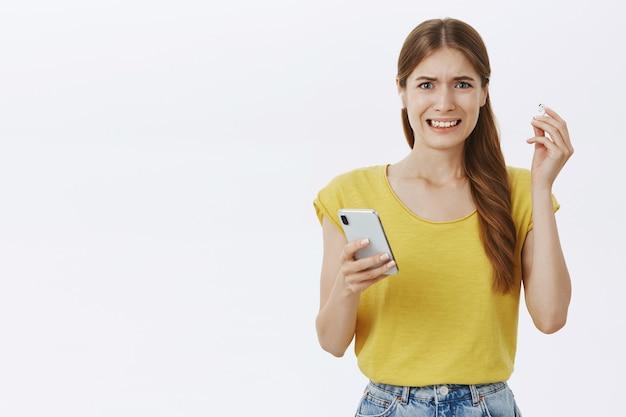 Niezadowolona i narzekająca gin girl zdejmuje słuchawkę i krzywi się z okropnej muzyki, trzymając smartfon