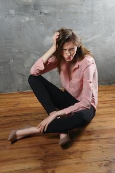Niezadowolona i nieszczęśliwa dziewczyna siedzi na podłodze z poskręcaną twarzą