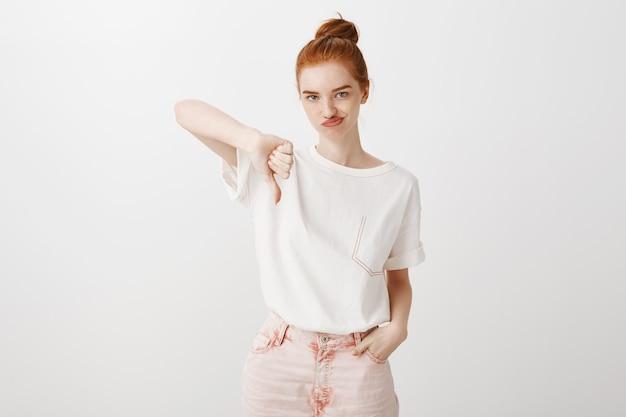 Niezadowolona i niewzruszona ruda dziewczyna pokazująca kciuk w dół z niechęcią