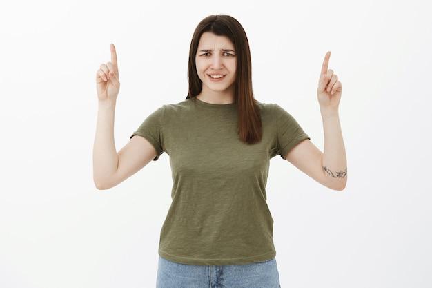 Niezadowolona i rozczarowana młoda kobieta skierowana w górę