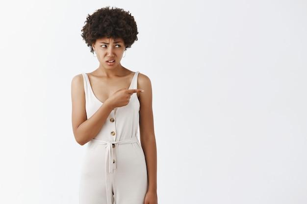 Niezadowolona i sfrustrowana stylowa dziewczyna pozuje pod białą ścianą