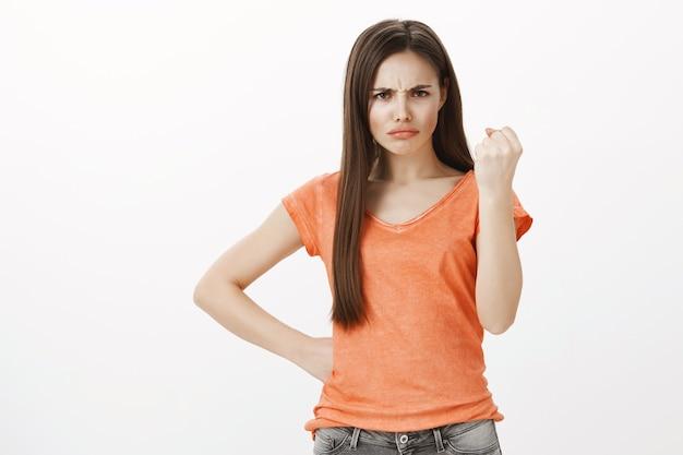 Niezadowolona i wściekła śliczna dziewczyna potrząsa palcem i marszczy brwi, beszta osobę, grozi karą