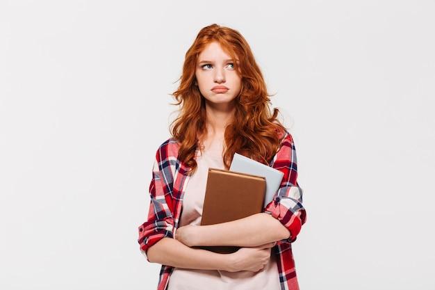 Niezadowolona imbirowa kobieta w koszuli trzyma książki i odwraca wzrok