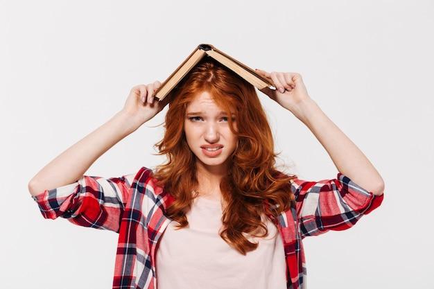 Niezadowolona imbirowa kobieta w koszuli, trzymając książkę na głowie