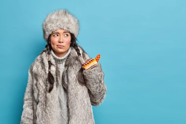 Niezadowolona inuicka kobieta w tradycyjnych zimowych ubraniach niechętnie patrzy i wskazuje na puste miejsce na tle niebieskiej ściany studia