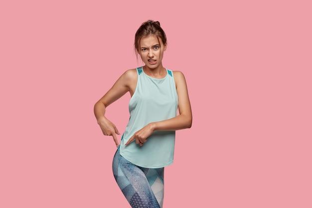 Niezadowolona kaukaska kobieta marszczy brwi z niezadowoleniem, wskazuje palcami wskazującymi na pośladki, stoi bokiem, modelki na różowej ścianie. koncepcja kształtu ciała i figury