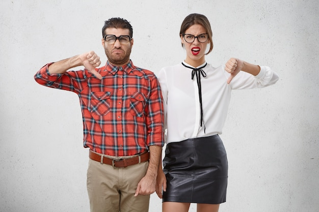 Niezadowolona kobieta i mężczyzna trzymają kciuki w dół, coś potępiają, marszczą brwi