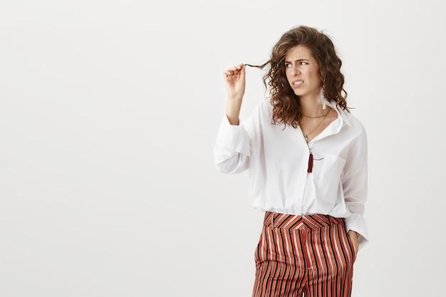 Niezadowolona kobieta patrząc na pasmo włosów, potrzebuje nowej fryzury