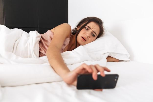 Niezadowolona kobieta patrząc na telefon komórkowy, śpiąc w łóżku na białej pościeli