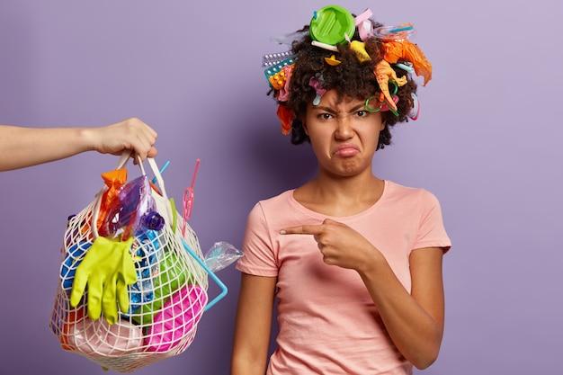 Niezadowolona kobieta pozuje ze śmieciami we włosach