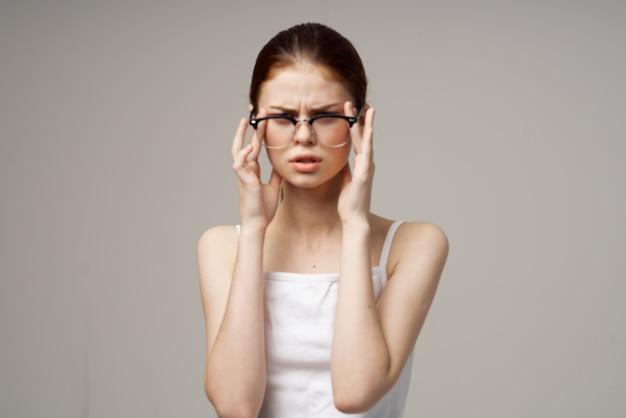 Niezadowolona kobieta problemy ze wzrokiem krótkowzroczność jasne tło