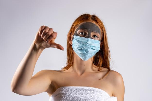 Niezadowolona kobieta w glinie i masce medycznej na białej ścianie koncepcja piękna i walki