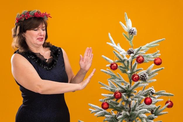 Niezadowolona kobieta w średnim wieku ubrana w świąteczny wieniec na głowę i świecącą girlandę wokół szyi, stojąca w pobliżu udekorowanej choinki