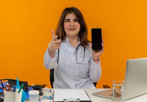 Niezadowolona kobieta w średnim wieku ubrana w szlafrok medyczny ze stetoskopem siedząca przy biurku na laptopie z narzędziami medycznymi trzymająca telefon i pokazująca gest na pomarańczowej ścianie