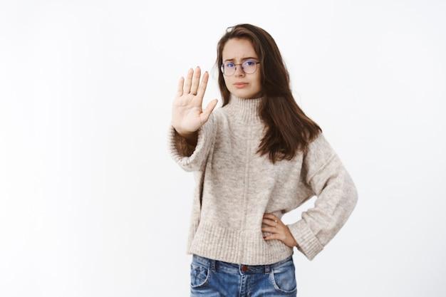 Niezadowolona kobieta wyrażająca niechęć i niechęć wyciągając rękę w geście zatrzymania marszcząc brwi z niechęci i osądu odrzucając i zabraniając czegoś wątpliwego nad szarą ścianą.