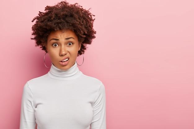 Niezadowolona kobieta z fryzurą w stylu afro, uśmiechnięta twarz
