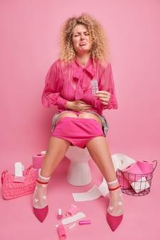 Niezadowolona kobieta z kręconymi włosami cierpi na ból brzucha trzyma środki przeciwbólowe siedzi na muszli klozetowej ubrana w modną bluzkę buty na wysokim obcasie źle się czuje