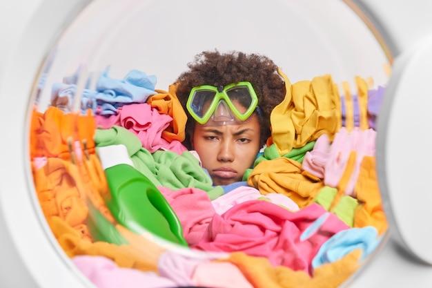 Niezadowolona kobieta z kręconymi włosami czuje się bardzo zmęczona, nosi okulary do nurkowania, pozuje wokół wielokolorowego prania w pralce, ładuje brudne ubrania do pralki, wyczerpana po pracach domowych
