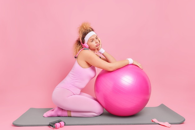 Niezadowolona kobieta z kręconymi włosami czuje się zmęczona po treningu fitness pochyla się na szwajcarskiej piłce
