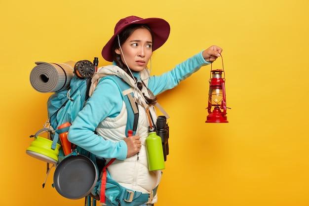 Niezadowolona kobieta z plecakiem rasy mieszanej nosi stylowy kapelusz i ciepłą kamizelkę, trzyma lampę naftową do odkrywania otoczenia w ciemności