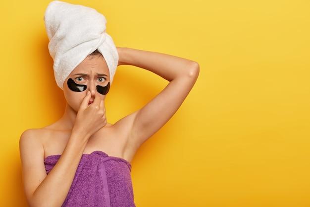 Niezadowolona kobieta zakrywa nos, marszczy brwi z powodu nieprzyjemnego zapachu, ma spoconą skórę, musi się wykąpać, owinięta ręcznikiem, napina skórę