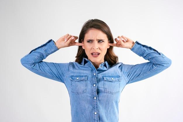 Niezadowolona kobieta zakrywająca uszy