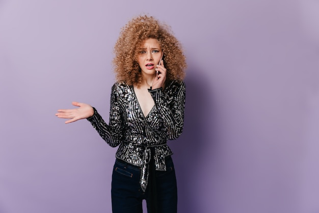 Niezadowolona kręcona blond kobieta w lśniącej bluzce z długimi rękawami rozmawia przez telefon na liliowej przestrzeni.