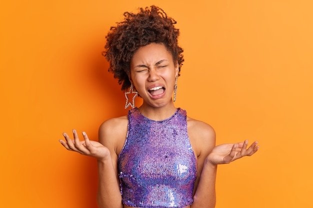Niezadowolona, kręcona młoda kobieta rozkłada dłonie i czuje sfrustrowany płacz, ponieważ nie widzi wyjścia, nosi modne fioletowe ubrania, które sprawiają, że fryzura ma pechowy dzień odizolowany od pomarańczowej ściany