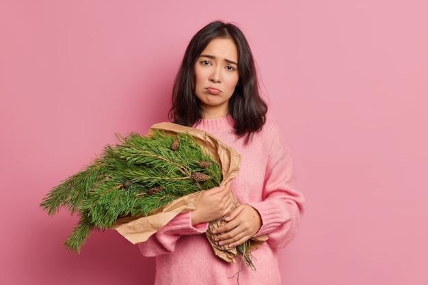 Niezadowolona kwiaciarka nosi gałęzie jodły, aby zrobić świąteczny wieniec, wygląda nieszczęśliwie w aparacie, przygotowuje piękną świąteczną kompozycję do dekoracji domu, nosi sweter z długimi rękawami