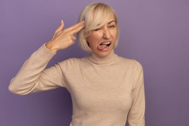 Niezadowolona ładna blondynka słowiańska kobieta wystawia język i gestykuluje ręką znak pistoletu, kładąc w świątyni na fioletowo