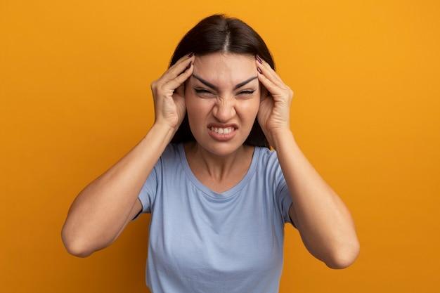 Niezadowolona ładna brunetka kobieta kładzie ręce na skroniach odizolowanych na pomarańczowej ścianie