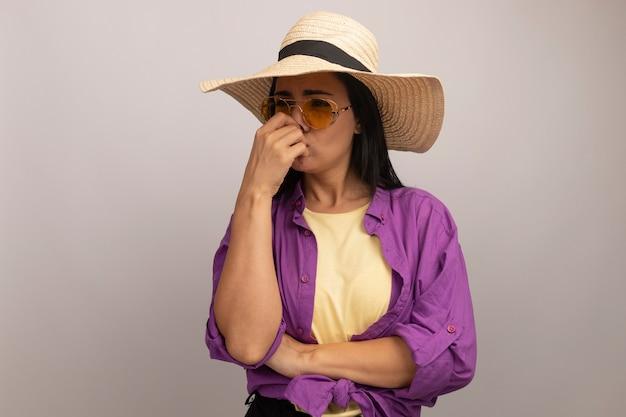 Niezadowolona ładna brunetka kobieta w okularach przeciwsłonecznych z kapeluszem plażowym zamyka nos i patrzy w bok na białej ścianie