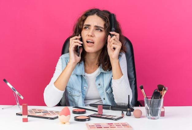 Niezadowolona ładna kaukaska kobieta siedzi przy stole z narzędziami do makijażu, rozmawia przez telefon, czesząc włosy