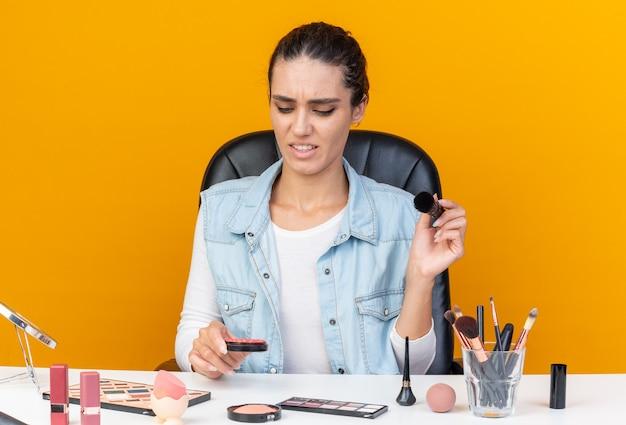 Niezadowolona ładna kaukaska kobieta siedzi przy stole z narzędziami do makijażu, trzymając pędzel do makijażu i patrząc na rumieniec odizolowany na pomarańczowej ścianie z miejscem na kopię
