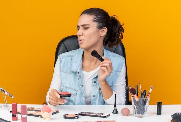 Niezadowolona ładna kaukaska kobieta siedzi przy stole z narzędziami do makijażu, trzymając pędzel do makijażu i rumieniec, patrząc na bok izolowane na pomarańczowej ścianie z kopią miejsca