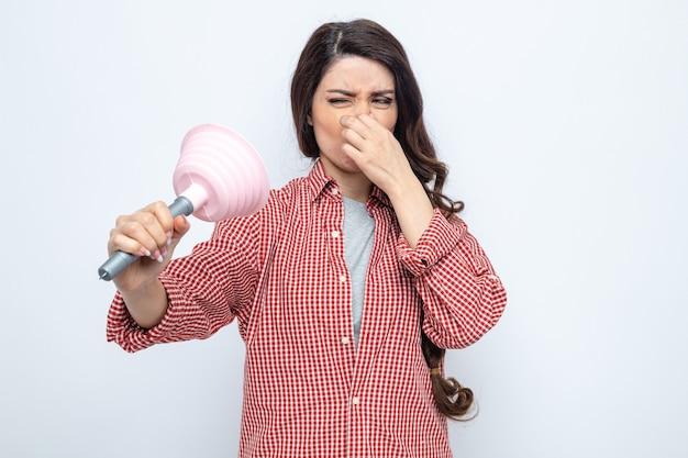 Niezadowolona ładna kaukaska sprzątaczka trzymająca gumowy tłok i zamykająca nos